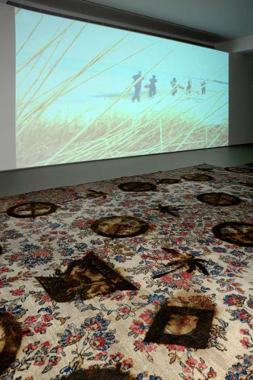 Rashid Johnson. The New Black Yoga Installation, 2011. 16mm film transferred to DVD, sound, 10 minutes 57 seconds. Branded Persian rugs, 27.9 x 35.6m. © Rashid Johnson. Courtesy the artist and Hauser & Wirth. Photograph: Rebecca Constantopoulou and Fanis Vlastaras.
