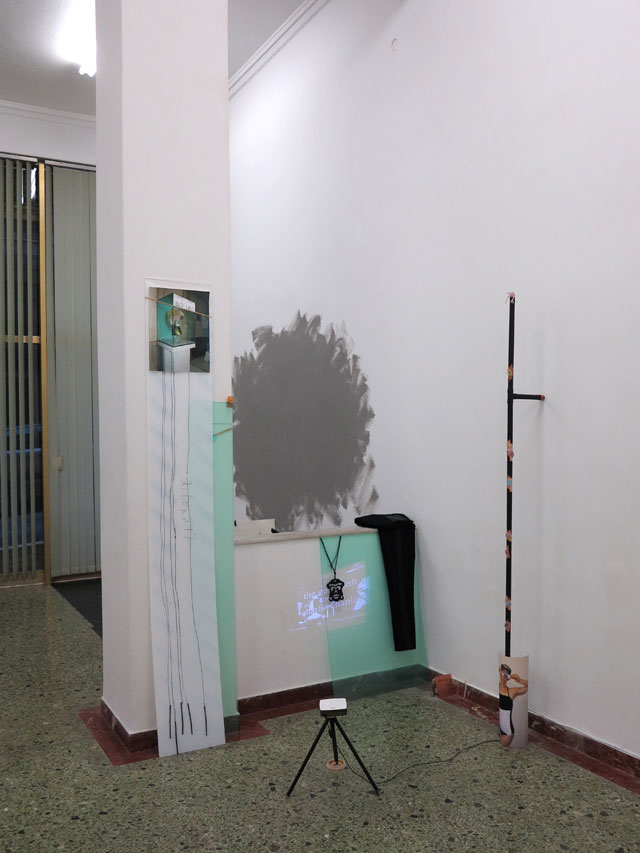 Sophie Jung. Cos of the Grand Change, 2014. Mixed media installation, performance (youtube video oceana roll, necklace, charcoal, perspex, photograph, finger puppet, COS jeggins, paint lid, New Balance shoes, glow-in-the-dark FIMO, blue tac, architect's sand, tar paint, oxidising paint, garfield cartoon, video, magnetic paint). Photograph: Sophie Jung.
