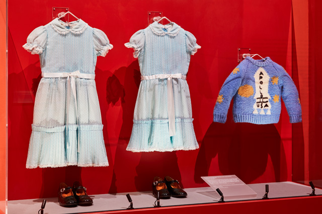 Grady sisters' costumes and Danny's jumper, original costumes from The Shining, directed by Stanley Kubrick, 1980. Photo: Ed Reeve, courtesy of the Design Museum.