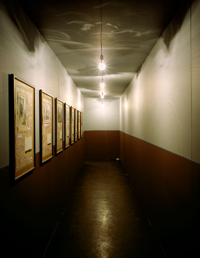 Ilya Kabakov. Labyrinth (My Mother's Album), 1990. Wooden construction, nine doors, wooden ceiling props, 24 light bulbs, detritus, audio and 76 works on paper, photographs, ink and printed papers. Tate collection. © Ilya & Emilia Kabakov.