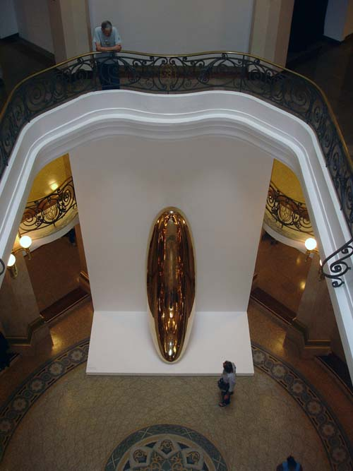 A visitor in the foyer of the CCBB Sao Paulo observes Anish Kapoor's Untitled at 'Ascension'. <em>Untitled</em>, 1999, brass, 445 x 124 x 108 cm