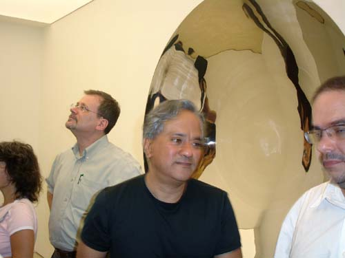 Anish Kapoor stops before his <em>Double mirror</em>, 1998. <em>Double Mirror</em>, 1998, stainless steel, two parts, 200 x 200 cm (each)
