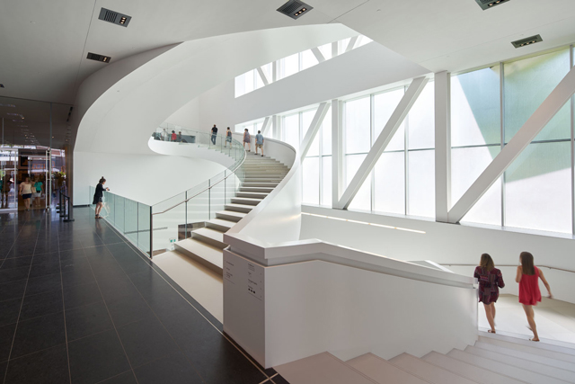 Pierre Lassonde Pavilion, Musée National des Beaux-Arts du Québec. 'The star of the Grand Hall is a glamorous white staircase.' Photograph: Bruce Damonte. © OMA.