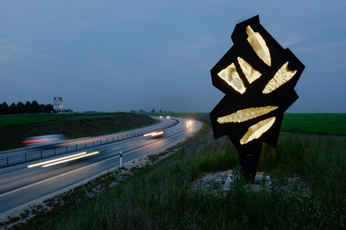 Bernard Lassus. Night photograph of motorway with sculpture.