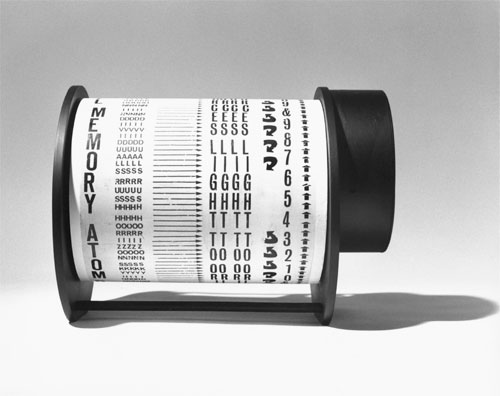 Liliane Lijn. Atom Born Beings Poem Machine, 1962/3. Letraset on painted metal drum, plastic, painted metal, motor, 24.8 x 30 x 25.4 cm. Words taken from a poem of Nazli Nour. Altered in 1963 or later - changed from box to a lighter frame of plastic discs and metal rods. Collection: The artist. Photograph: Liliane Lijn.