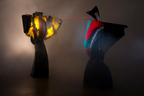 Liliane Lijn. Conjunction of Opposites: Lady of the Wild Things and Woman of War, 1986. Two mixed media performing sculptures enact a computer controlled 6 minute drama which includes movement, song, the transformation of sound to light, and a laser display, 400 x 800 x 400 cm (12 x 24 x 12 ft). First exhibited at the Art and Science Venice Biennale in 1986 in the Art, Technology, and Computers Section in the Arsenale.