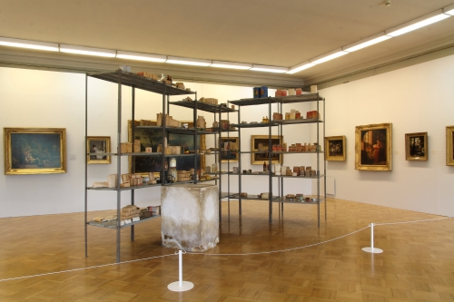 Joseph Beuys. Wirtschaftswerte (Economic Values), 1980. Iron shelves with basic food and tools from East Germany; plaster block with pencil and fat; paintings from the collection of the host museum. Shelves: 290 × 400 × 265 cm; Plaster block: 98.5 × 55.5 × 77.5 cm. Collection of S.M.A.K. Stedelijk Museum voor Actuele Kunst, Ghent, Belgium. Installation view, MANIFESTA 10, Winter Palace, State Hermitage Museum.