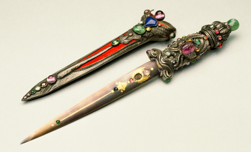Marie Zimmermann. Dagger and Scabbard, dated 1921. Dagger handle: silver, emerald, pink tourmalines, jade, pink sapphire, ruby, emerald, blue sapphire, citrine, garnet, chrysoberyl, unheated multi-colored corundum. Blade: damascened steel with gold, pink tourmaline, blue sapphire, jade or chrysoprase, garnet, blue sapphire. Scabbard: silver, bone, red velvet, amethyst, lapis lazuli, pink tourmaline or pink sapphire, ruby or garnet, chrysoberyl, emerald, jade. Dagger, 8 1/2 in. (21.6 cm); scabbard, 6 1/8 in (15.6 cm). Private collection. Photograph: David Cole © Svartvik Metalworks, Ltd. Used by permission.