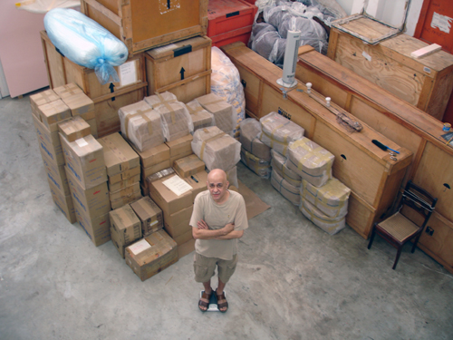 Cildo Meireles surrounded by the boxes which contain the first version of the