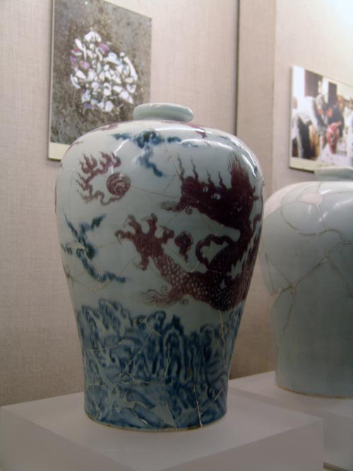 Blue and white and underglazed red cloud dragon design vase (Mei Ping). Ming dynasty Yongle (1403-24). Height: 34.1 cm. Diameter at mouth: 6.7 cm. Diameter at base: 15.9 cm. This vase (Mei Ping) has a very small mouth, short neck, wide shoulder and small base with a round rim. The mouth is so small that only a single stem of plum blossoms would fit inside. This type of porcelain has thus been named 'Mei Ping', or 'plum-blossom vase'. In fact, vessels of this type were wine containers and very popular during the Ming and Qing dynasties. The design of this vase is uniquely done with blue and white mountains and waves in the lower part, an underglazed red dragon on the main body and clouds on the shoulders.