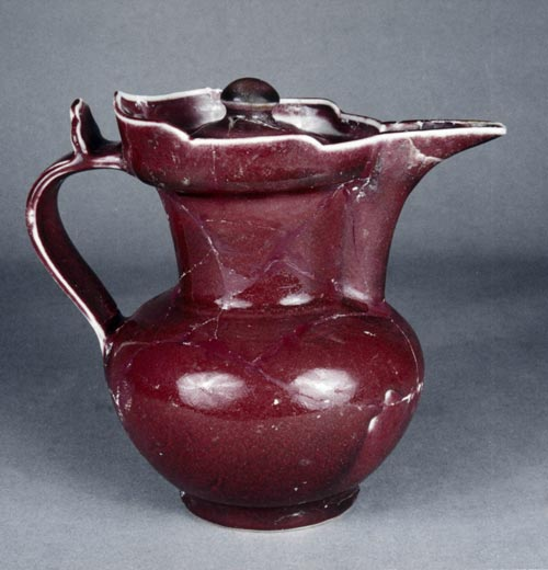 Monk's cap-shaped pot with red glaze. Ming dynasty Yongle (1403-24). Height: 19 cm. Diameter at mouth: 11.2 cm. Diameter at base: 8 cm. The mouth of the jar seemed slightly like a cap of monk and so it was named. It is covered with red glazed but uneven.