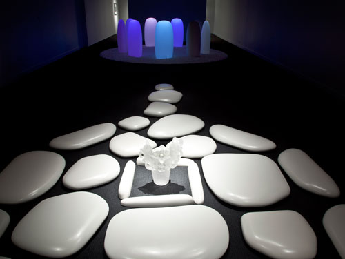 Mariko Mori. FOREGROUND: Flatstone, 2006. Ceramic stones and acrylic vase; 192 × 124 × 3 1/2 inches. Courtesy of SCAI THE BATHHOUSE, Tokyo and Sean Kelly, New York. BACKGROUND: Transcircle 1.1, 2004. Stone, Corian, LED, real-time control system; 132 3/8 inches diam., each stone 43 3/8 × 22 1/4 × 13 1/2 inches. Courtesy of The Mori Art Museum, Tokyo. Installation photograph: Richard Goodbody.