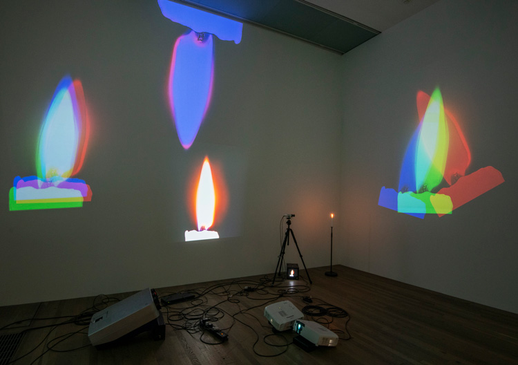 Nam June Paik. One Candle (Candle Projection) 1989. Installation view, Tate Modern 2019. Close-circuit television camera, tripod, candle on custom stand and four to six colour video projectors including modified CRT projectors. Museum für Moderne Kunst, Frankfurt am Main.