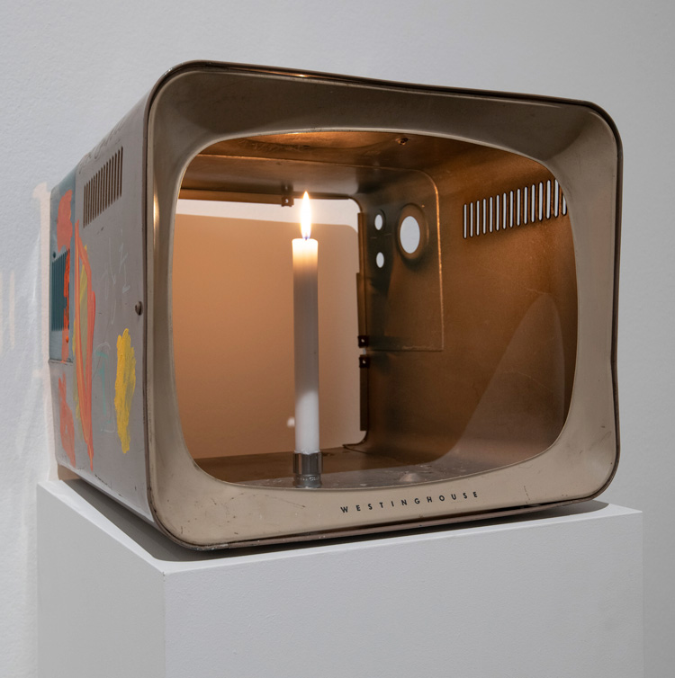Nam June Paik. One Candle (also known as Candle TV) 2004. Installation view, Tate Modern 2019. Cathode-ray tube television casing with additions in permanent oil marker, acrylic paint and live candle, 35.6 x 40.6 x 40.6 cm. Courtesy the Estate of Nam June Paik. Photo: © Tate (Andrew Dunkley).