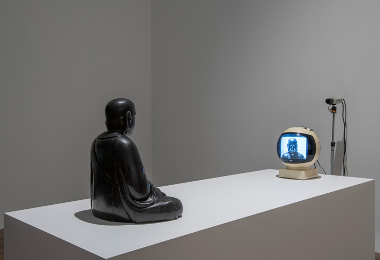 Nam June Paik. TV Buddha 1974. Installation view, Tate Modern 2019. 18th century wooden sculpture, closed-circuit television camera and JVC Videosphere cathode-ray tube television. Stedelijk Museum, Amsterdam. Photo: © Tate (Andrew Dunkley).