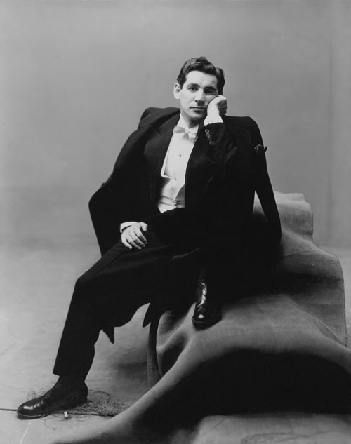Leonard Bernstein, conductor and composer, wearing a tuxedo, sitting on a group of carpeted boxes. Portraits of people of the