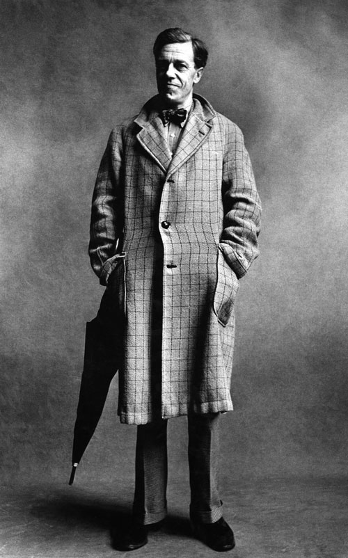 Cecil Day Lewis, poet, wearing a three-button, checked overcoat, hands in the pockets, with an umbrella.
