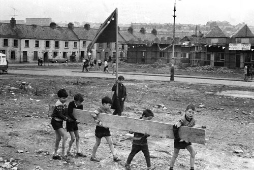 Eamon Melaugh. These children are either engaged in strengthening street barricades or bringing some firewood home for the house. The boy with the flag is striking a particularly good revolutionary pose for one so young! Note the 'Derry Merry, Derry Free' banner in the background. The photograph may have been taken around the time of the Liberation Fleadh, 30 August 1969. Lecky Road, Bogside, Derry.