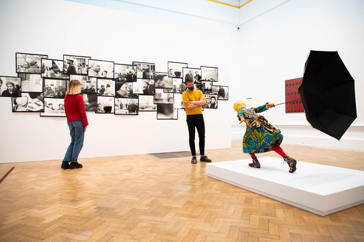Left: Isaac Julien. Lessons of the Hour, London 1983 – Who killed Colin Roach?; Right: Yinka Shonibare. Air Kid (Girl). Installation view RA Summer Exhibition 2020. Photo: © Royal Academy of Arts / David Parry