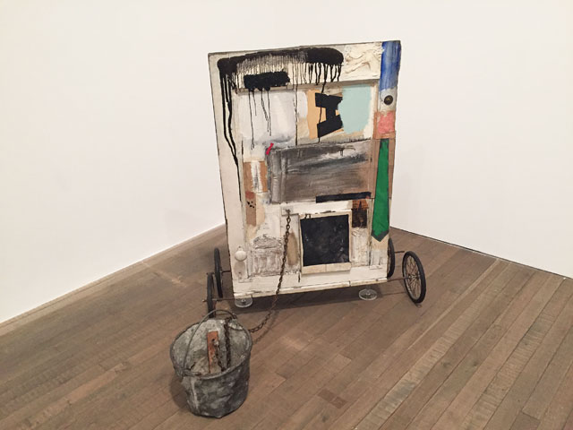 Robert Rauschenberg. Gift for Apollo, 1959. Oil paint, wood, fabric, newspaper, printed reproductions on wood with metal bucket, metal chain, door knob, L brackets, metal washer, nail and rubber wheels with metal spokes. 11.1 x 74.9 x 104.1 cm. The Museum of Contemporary Art, Los Angeles, The Panza Collection. Photograph: Martin Kennedy.