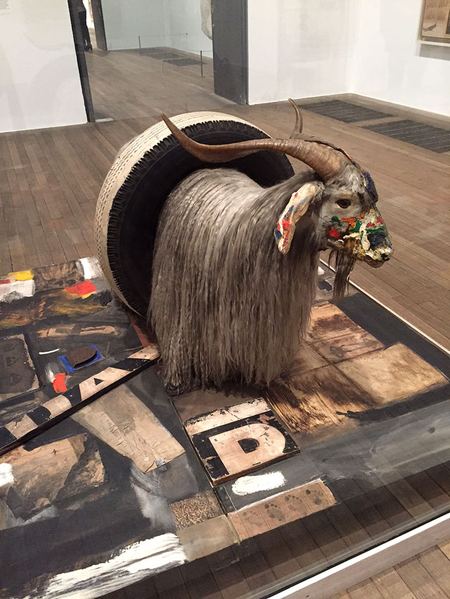 Robert Rauschenberg. Monogram, 1955-59. Oil paint on taxidermied angora goat and rubber tire, on oil paint on paper, fabric printed paper, printed reproductions, metal, wood, rubber shoe heel, and tennis ball on canvas on wood platform mounted on four casters, 129 x 186 x 186 cm. Moderna Museet, Stockholm. Photograph: Martin Kennedy.