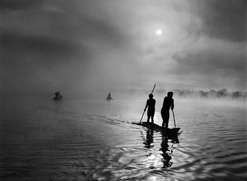 Sebastião Salgado. In the Upper Xingu region of Brazil's Mato Grosso state, a group of waura fish in the Piulaga Lake near their village. The Upper Xingu Basin is home to an ethnically diverse population. Brazil, 2005. © Sebastião Salgado/Amazonas Images/nbpictures