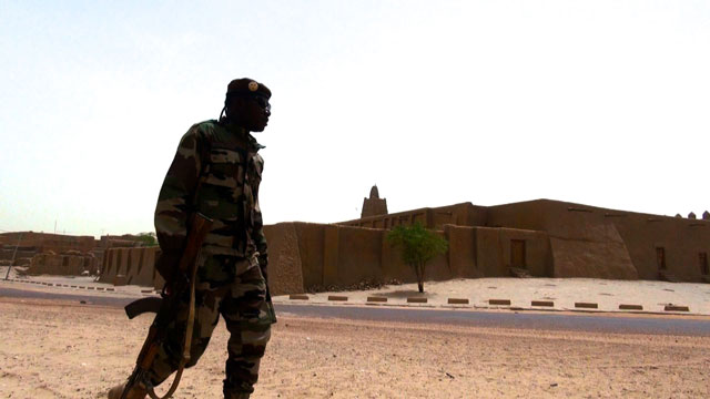 A Malian soldier patrols the reconstructed tombs of Timbuktu, destroyed by extremists in 2012.