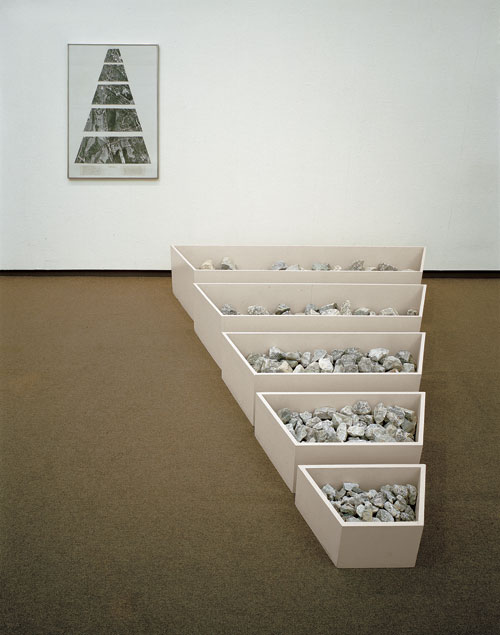Robert Smithson. A Nonsite (Franklin, New Jersey), 1968. Painted wooden bins, limestone, gelatin-silver prints and typescript on paper with graphite and transfer letters, mounted on mat board. Bins installed: 16 ½ x 82 ¼ x 103 in. (41.9 x 208.9 x 261.6 cm). Framed: 40 ¾ x 30 ¾ x 1 in. (103.5 x 78.1 x 2.5 cm). Sheet: 39 7/8 x 29 7/8 in. (101.3 x 75.9 cm). Collection Museum of Contemporary Art Chicago, gift of Susan and Lewis Manilow  1979. Photograph: James Isberner, © Museum of Contemporary Art Chicago. Image courtesy James Cohan Gallery, New York/Shanghai.