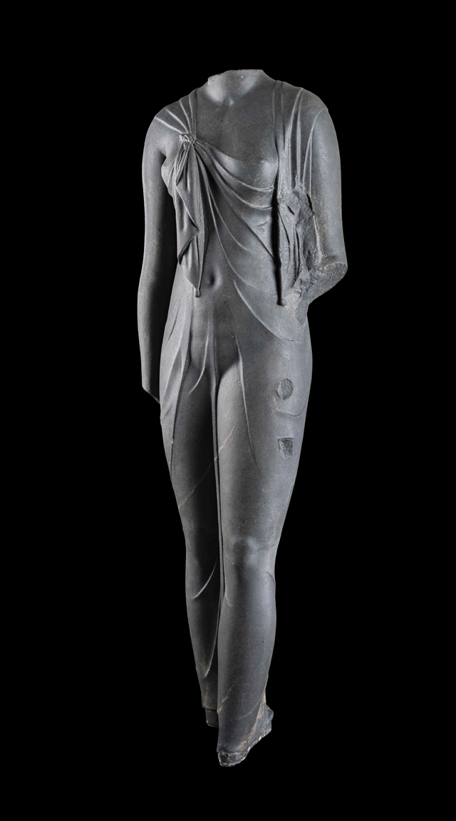 Statue of Arsinoe, Canopus, Aboukir Bay, Egypt (SCA 208). Cut in hard, dark stone, this feminine body has a startlingly sculptural quality. Complete, it must have been slightly larger than life-size. The statue is certainly one of the queens of the Ptolemaic dynasty (likely Arsinoe II) dressed as the goddess Isis, as confirmed by the knot that joins the ends of the shawl the woman wears, which was representative of the queens during this time period. The statue was found at the site of Canopus. © Franck Goddio/Hilti Foundation. Photograph: Christoph Gerigk.