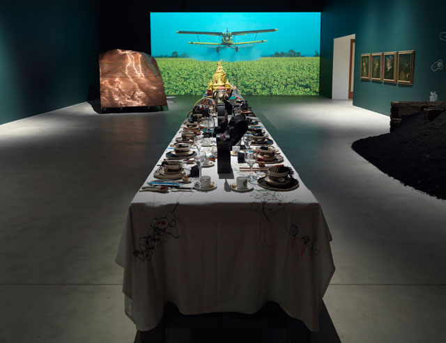 Background: Nikolaus Geyrhalter's Our Daily Bread, 2005; Foreground: Table with amalgamation of many artists' work, including that of Ryan Gander, Rob Kesseler, Laure Prouvost, Williams and Aaron Angell. Courtesy of Hauser & Wirth. Photograph: Ken Adlard.