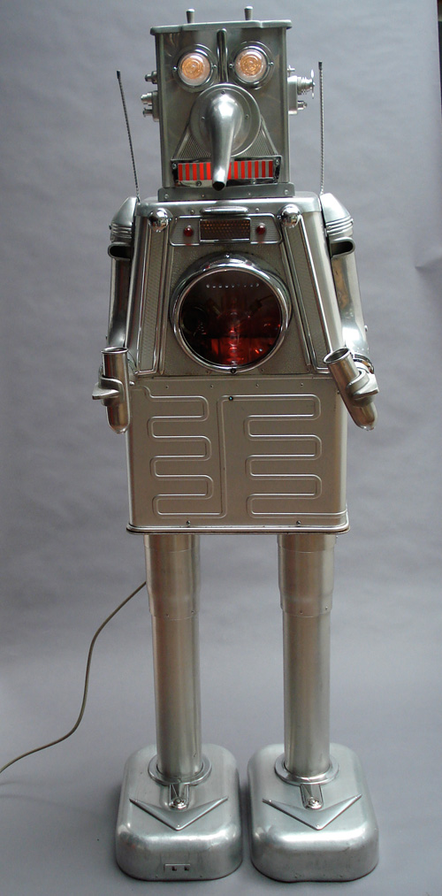 Clayton Bailey. Milker Robot, 1985. Repurposed scrap aluminium, chrome, stainless steel, glass, light bulbs, 67 x 20 x 17 in. Courtesy of the artist. © Clayton Bailey.