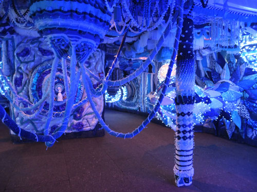 Joana Vaconselos. Decommissioned ferry, exterior covered in typical Portuguese blue and white tiles showing a Lisbon panorama. Ship's hold transformed into a fuzzy blue womb of crochet and fairy lights, with padded walls and giant pompoms hanging from above. Photograph: Dorothy Feaver.