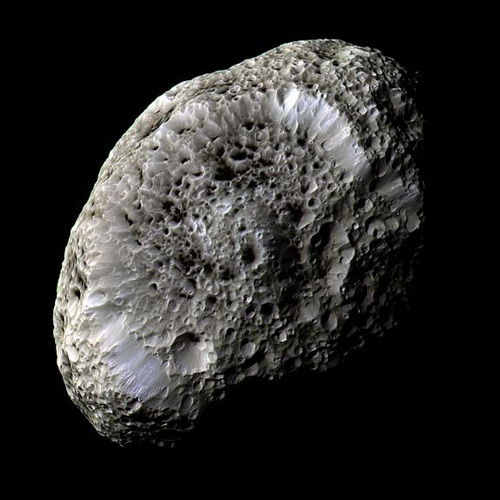 Hyperion. Cassini orbiter spacecraft, 2005. Imaging Science Subsystem – Narrow Angle (enhanced colour image). This sponge-like object is one of the most bizarre of Saturn's family of over sixty moons. Over 360 km from end to end, Hyperion is made largely of ice and has the consistency of a loose pile of rubble. Its surface is covered with irregular sharp-edged craters dusted with a mysterious dark material which may have originated on Phoebe, another of Saturn's moons. © NASA/JPL/Space Science Institute: http://photojournal.jpl.nasa.gov/catalog/PIA07740