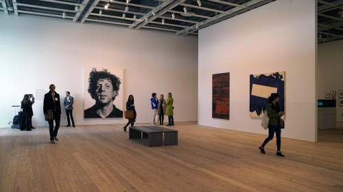 Whitney Museum. Installation view. Back: Chuck Close. Phil, 1969. Acrylic and graphite pencil on canvas, 108 1/4 × 84 in (275 × 213.4 cm). Whitney Museum of American Art, New York; Purchase, with funds from Mrs. Robert M. Benjamin. Photograph: Miguel Benavides.