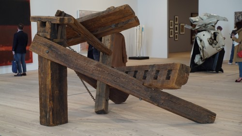 Exhibition view, including Mark di Suvero. Hankchampion, 1960. Wood, steel hardware and chains, 77 1/2 × 152 × 109 3/16 in. (196.9 × 386.1 × 277.3 cm). Whitney Museum of American Art, New York; Gift of Mr. and Mrs. Robert C. Scull. Photograph: Miguel Benavides.